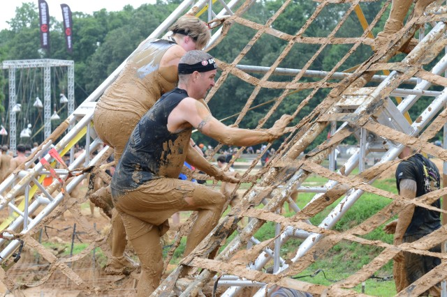 Command Sgt. Maj. David O. Turnbull, U.S. Army Military District of Washington command sergeant major, climbs a net obstacle during the four-mile Spartan sprint event held at Wicomico Motorsports Park in Charlotte Hall, Md., July 26, 2014.