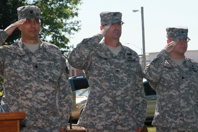 Lt. Col. Larry Cannon (left to right), Col. Joseph Dalessio and Lt. Col. Shane Upton render honors during the playing of the National Anthem at the Lake City Army Ammunition Plant, Missouri, change of command ceremony, July 23. Dalessio is the commander of McAlester Army Ammunition Plant, Oklahoma, the higher headquarters for LCAAP, and was the host for the ceremony.