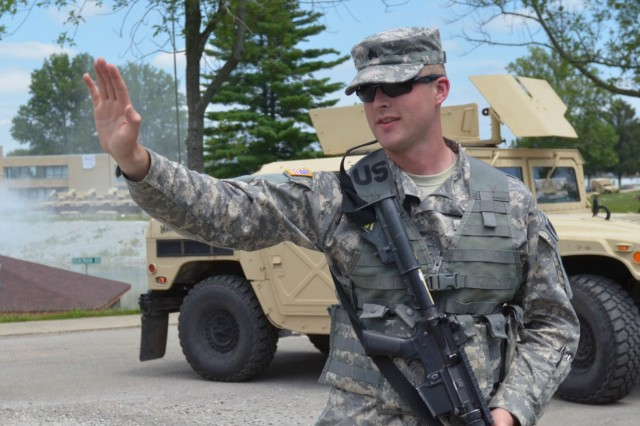 Sgt. James Crisp, a military police officer assigned to 384th Military Police Company, Indiana Army National Guard, attempts to stop a vehicle at simulated traffic control point at Muscatatuck Urban Training Complex, Ind., July 25, 2014. Vibrant Response is a major field training exercise conducted by the U.S. Northern Command and led by U.S. Army North. Approximately 5,000 service members and civilians from the military and other federal and state agencies throughout the country are training to respond to a catastrophic domestic incident. As a component of U.S. Northern Command, Army North coordinates timely federal and military response to disasters in the homeland to help the American people in a time of need. (U.S. Army photo by Sgt. Brandon Anderson 13th Public Affairs Detachment/Released)