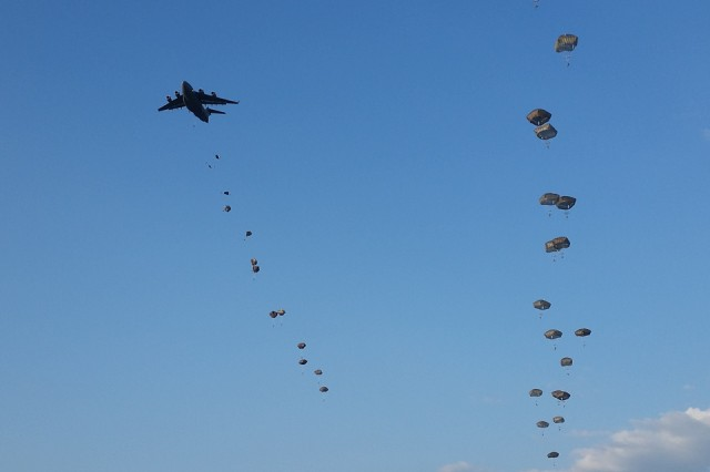 Paratroopers assigned to 3rd Battalion, 319th Airborne Field Artillery Regiment, 1st Brigade Combat Team, 82nd Airborne Division, exit a C-17 Globemaster over Holland Drop Zone, July 29, at Fort Bragg, N.C. (U.S. Army photo by Staff Sgt. Mary S. Katzenberger)