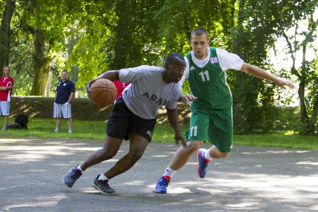 Spc. Reginald Davis dribbles a basketball during a half-court basketball game with Latvian soldiers at the Latvian National Guard's annual sports competition in Augstkalne, Latvia, July 19.