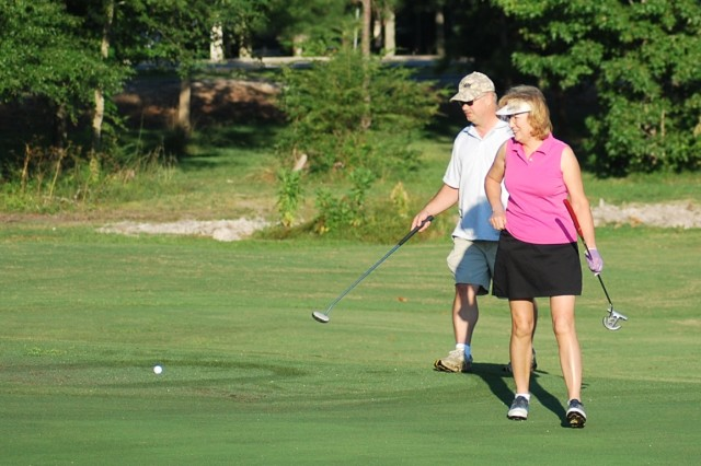 (Left) Mark Smith, ACC Office of the Inspector General, and Belinda Gemme, ACC Deputy Chief of Staff Resource Management G-8, look over the green prior to attempting a putt.
