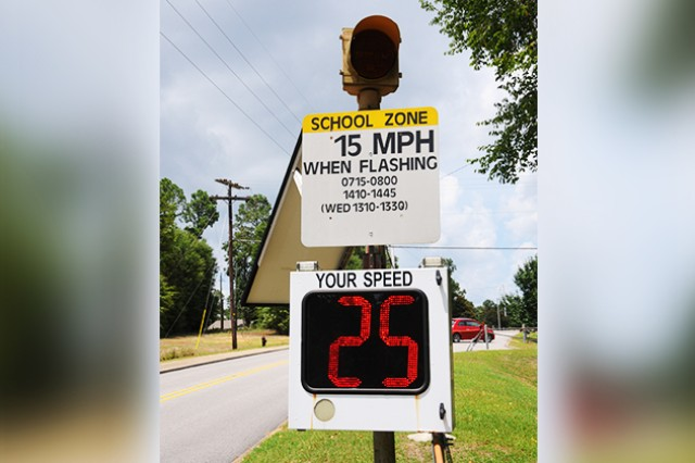 A school zone speed monitor flashes as a driver passes through the area.