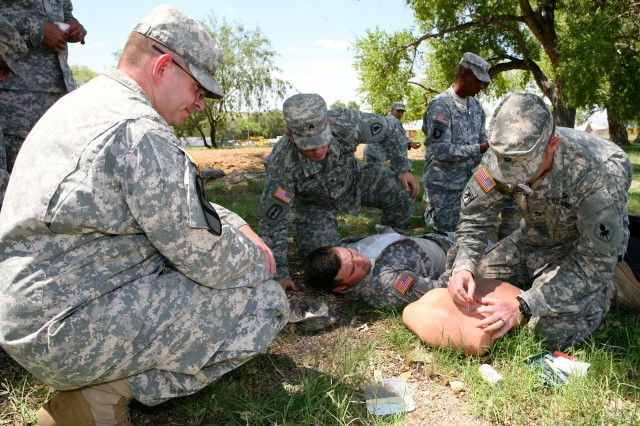 As his classmates assist, Sgt. 1st Class Jon Wood, U.S. Army Intelligence Center of Excellence, inserts a chest needle into a medical simulator to relieve pressure of the lunch cavity as his classmates provide support and guidance, during the Combat Lifesaver Course on Fort Huachuca July 25.