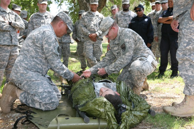 From left, Fort Huachuca Combat Lifesaver Course instructors Sgt. James Atcitty, U.S. Army Medical Department Activity, and Sgt. James Fender, 111th Military Intelligence Brigade, wrap a casualty in a heat protective shell during the final event of the Combat Lifesaver Course, July 25. The shell is used to prevent hypothermia following a combat-related incident.