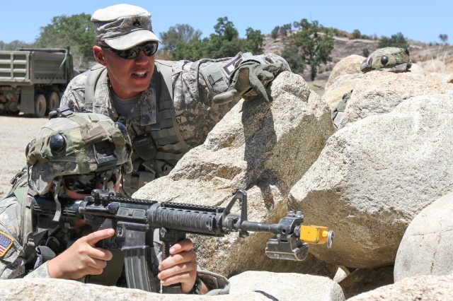 Staff Sgt. Zachariah Hussey (top), an observer-coach/trainer with 2nd Battalion, 357th Infantry Regiment, 189th Infantry Brigade, reviews sectors of fire with Reserve Sgt. Megan Moore, a team leader assigned to the 338th Engineer Company, during Warrior Exercise 2014 at Fort Hunter-Liggett, California, July 24. The 189th Infantry O-C/Ts provided feedback and facilitated training for more than 4,000 support Soldiers from the active duty, Reserve and National Guard components during the 14-day exercise.