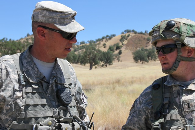 Staff Sgt. Zachariah Hussey (left), an observer-coach/trainer with 2nd Battalion, 357th Infantry Regiment, 189th Infantry Brigade, talks with Reserve 1st Lt. Robert Kelly, a platoon leader with the 338th Engineer Company, during Warrior Exercise 2014 at Fort Hunter-Liggett, California, July 24. The 189th Infantry Brigade, headquartered at Joint Base Lewis-McChord, Washington, provided O-C/Ts for the 14-day exercise designed for support units from the active, National Guard and Reserve components.