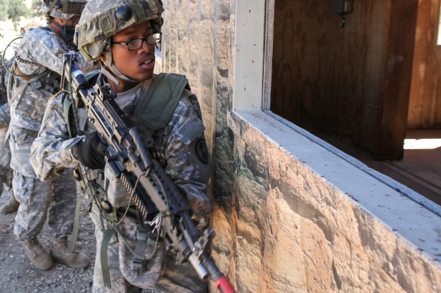 Army Reserve Pfc. Jaquau Stanley, an M249 machine-gunner with the 377th Military Police Company, clears a window during Warrior Exercise 2014 at Fort Hunter-Liggett, California, July 22. More than 40 active, Reserve and National Guard support units from across the country participated in the 14-day exercise.