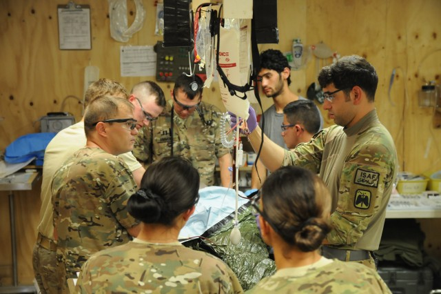 FOB PASAB, Afghanistan --Doctors and medics of the 3rd Squadron, 61st Cavalry Regiment, 4th Infantry Brigade Combat Team, 4th Infantry Division, Destroyer Aid Station, wrap a patient to control his body temperature during medical evacuation July 16, 2014. The Destroyer Aid Station has worked alongside their Afghan National Army partners helping many patients.