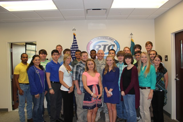 Summer interns pose with Col. Patrick Mason, Commander of the Redstone Test Center, in front of the RTC logo after a day of professional development.