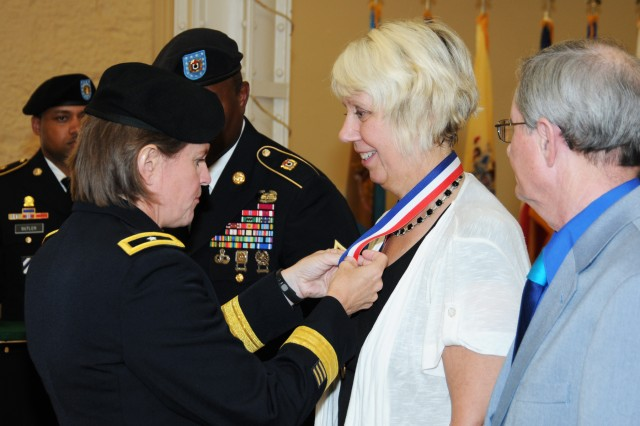 Brig. Gen. Kristin K. French, commanding general, Joint Munitions Command, places the civilian retirement pin on Joyce Paustian, recognizing her 36 years of service to the Department of Defense. Observing during the Rock Island Arsenal Retirement and Retreat ceremony is her fiancé, Woody Perkins.