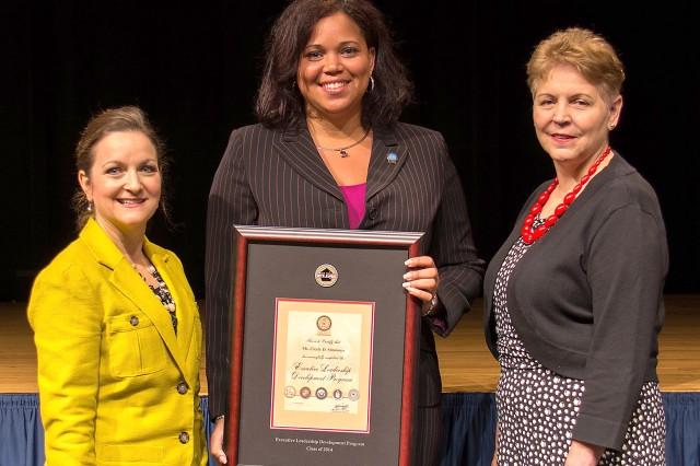Cicely Simmons is presented a certificate from the Honorable Jessica Wright, right, and Paige Hinkle-Bowles, left, for completion of the DOD Executive Leadership Development Program. Wright is the acting under secretary of Defense for personnel and readiness, and Hinkle-Bowles is the deputy assistant secretary of Defense for civilian personnel policy.
