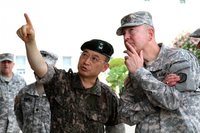 The 19th Expeditionary Sustainment commander, Brig. Gen. Stephen E. Farmen, is given insight by Republic of Korea army Brig. Gen. Kim Yo-hwang, during senior leader development as the Korean Defense Intelligence Command displayed a North Korean special operations forces infiltration, van Aug. 1, staged in front of the headquarters of the 19th ESC for more than 130 Soldiers, here. The KDIC's 40-foot SOF infiltration van displayed a collection of items ranging from clothing, communication devices, weapons, and under water equipment, retrieved from real-life infiltration attempts by North Korean Soldiers. (Photo by Staff Sgt. Cashmere Jefferson, 19th Expeditionary Sustainment Command Public Affairs Office)