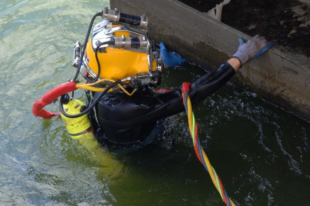 Diver Dustin Kelley, Nashville District Dive Team, inspects the lock gate after the gate shook and experienced a malfunction early in the morning at Pickwick Lock in Counce, Tenn., July 28, 2014. (USACE photo by Leon Roberts)