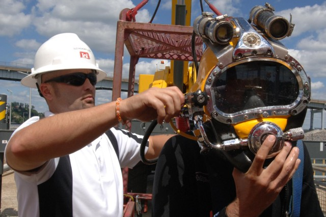 Jeff Neely, Nashville District Dive Team member, prepares to remove the diving helmet from Dustin Kelley after he completed his dive to inspect the lock gate at Pickwick Lock in Counce, Tenn., July 28, 2014. (USACE photo by Leon Roberts)