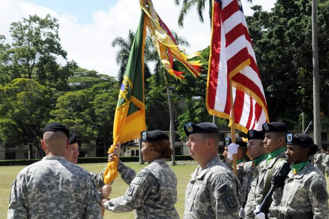 SCHOFIELD BARRACKS, Hawaii - Col. Duane Miller, commander, 8th Military Police Brigade, returns the unit colors to the incoming command sergeant major, Command Sgt. Maj. Angelia Flournoy, signifying Col. Miller's trust and confidence in the noncommissioned officers of the brigade; delegating authority and entrusting Command Sgt. Maj. Flournoy with the responsibility of the 8th MP Bde. (Photo by Staff Sgt. Richard Sherba, 8th Military Police Brigade Public Affairs, 8th Theater Sustainment Command)