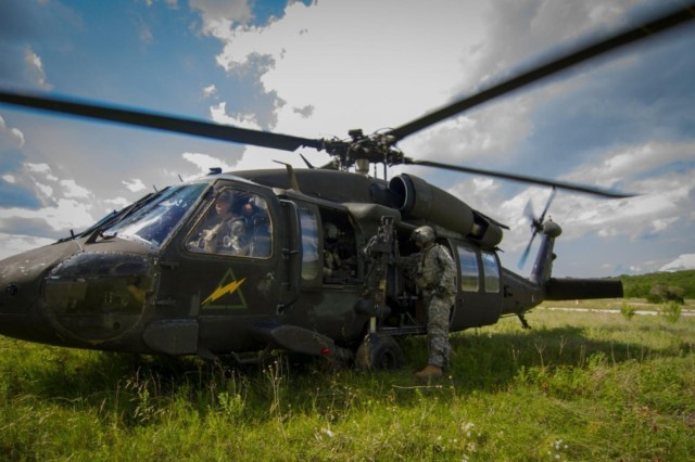 Staff Sgt. Joel Redman, the squadron standardization instructor for the 3rd Attack Helicopter Battalion, 227th Aviation Regiment, Air Cavalry Brigade, 1st Cavalry Division, on Fort Hood, Texas, climbs back into the UH-60 Black Hawk helicopter after reloading the M240H. The aircraft lands in order to reload weapon systems, for safety purposes during training.
