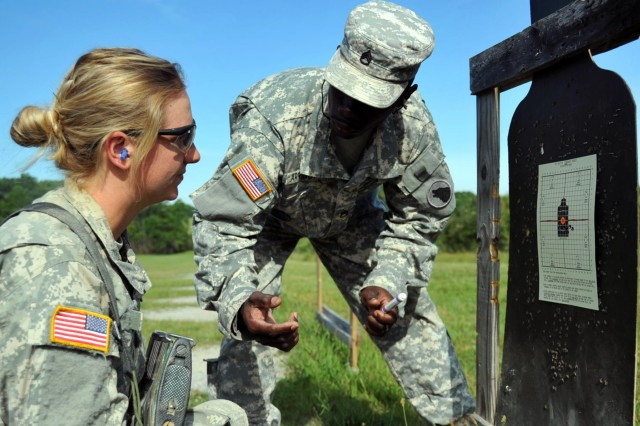 U.S. Army Staff Sgt. Raymond Arrington, instructor, basic rifle marksmanship committee, Task Force Wolf, explains to cadet Morgan Moxley, a Kansas State student, the necessary amount of rounds needed within a four centimeter circle in order to zero her weapon during Cadet Summer Training (CST) on Fort Knox, Ky., July 25. The basic rifle marksmanship committee, comprised of Reserve Soldiers from 1st Battalion, 323rd Infantry Regiment, 2nd Brigade, 98th Training Division (Initial Entry Training), teach cadets the fundamentals of BRM, facilitate the mechanical zero process, and coach them through the grouping, zeroing and qualification with their assigned M16 rifle. (U.S. Army photo by Staff Sgt. Shejal Pulivarti/released)