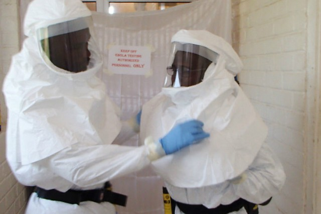 Aaron Momolu (left) and Lawrence Fakoli, Liberian laboratory technicians at the National Public Health Reference Lab, don personal protective equipment before entering a containment area to test samples.