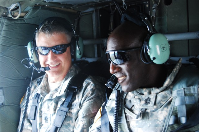 Sgt. Maj. of the Army Raymond F. Chandler III, left, and Command Sgt. Maj. James L. Manning Jr., with 2nd Battalion, 22nd Infantry Regiment, 1st Brigade Combat Team, ride in the back of a UH-60 Black Hawk helicopter, Aug. 5, 2014, above Fort Drum, N.Y. Chandler visited with Fort Drum and 10th Mountain Division (Light Infantry) Soldiers and family members and discussed the Army's Ready and Resilient Campaign.