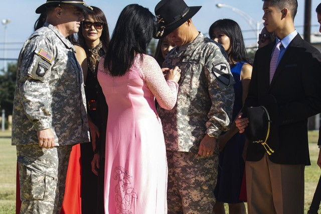 Kim Luong, wife of Brig. Gen. Viet Luong, deputy commanding general for maneuver, places the brigadier general rank on her husband during a promotion ceremony at Cooper Field, on Fort Hood, Texas, Aug. 6, 2014. Luong is the first Vietnamese-born general/ flag officer in the U.S. military. Luong credits his advancement in rank to the Soldiers and non-commissioned officers he has served with throughout the years.