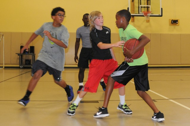 Nathaniel Belgrave tries to make a shot July 31 at the youth center as Dominic York defends and Mychal Moerkerken blocks.