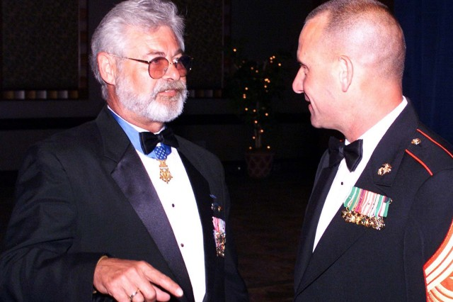 Medal of Honor recipient Jon R. Cavaiani (left), speaks with a U.S. Marine at a gathering, in 2004.