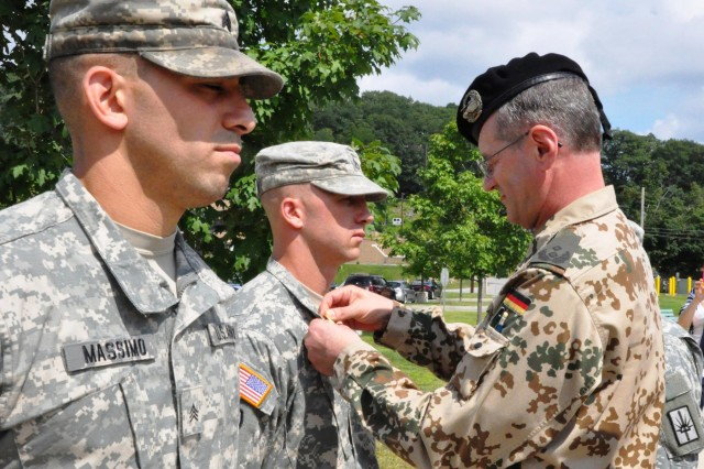 Lt. Col. Rolf Metz, German Army liaison officer to the United States Military Academy, West Point, N.Y. presents the German Armed Forces Proficiency Badge to New York Army National Guard Staff Sgt. Jeffrey Dorvee, 1427th Transportation Battalion, Queensbury, N.Y, during a ceremony at Camp Smith Training Site, N.Y., Aug. 3, 2014.  The decoration is traditionally awarded to German enlisted soldiers for weapons proficiency, and is one of the few foreign awards approved for wear by U.S. military personnel. Metz worked with 53rd Troop Command leaders to allow New York Army National Guard Soldiers to earn the coveted award in New York.