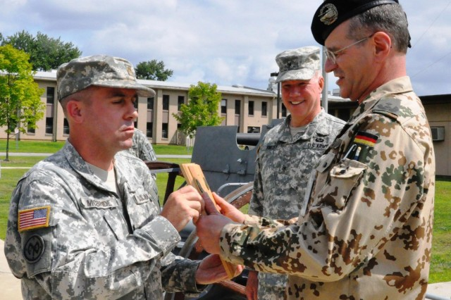 New York Army National Guard Maj. John McBride, assistant operations officer for the 53rd Troop Command (left), and Brig. General Michael Swezey, commander of the 53rd Troop Command, present Lt. Col. Rolf Metz, German Army liaison officer to the United States Military Academy, West Point, N.Y. with a plaque to convey appreciation for his support in establishing a program that allows New York Army National Guard Soldiers to earn the German Armed Forces Proficiency badge, at Camp Smith Training Site, N.Y., Aug. 3, 2014. The decoration is traditionally awarded to German enlisted soldiers for weapons proficiency, and is one of the few foreign awards approved for wear by U.S. military personnel. Metz worked with 53rd Troop Command leaders to allow New York Army National Guard Soldiers to earn the coveted award in New York.