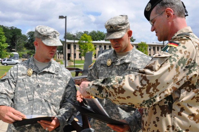 Lt. Col. Rolf Metz, German Army liaison officer to the United States Military Academy, West Point, N.Y., presents the German Armed Forces  Proficiency Badge certificate to New York Army National Guard Sgt. Sean Massimo, 442nd Military Police Company, Jamaica, N.Y., and Staff Sgt. Jeffrey Dorvee, 1427th Transportation Bn, Queensbury, N.Y., following the presentation of the badge during a ceremony at Camp Smith Training Site, N.Y., Aug. 3, 2014. The decoration is traditionally awarded to German enlisted soldiers for weapons proficiency, and is one of the few foreign awards approved for wear by U.S. military. Metz worked with 53rd Troop Command leaders to allow New York Army National Guard Soldiers to earn the coveted award in New York.