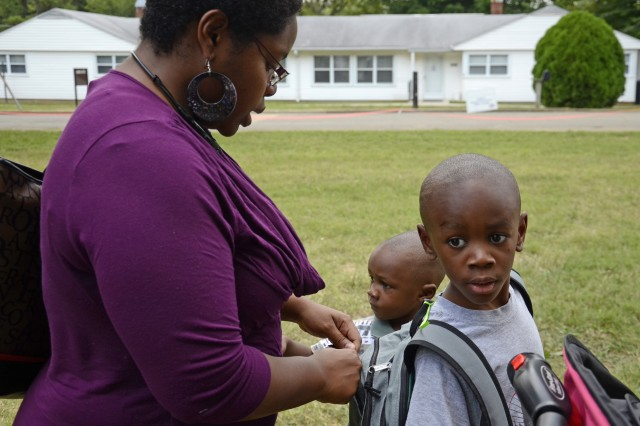 Military spouse Marquia Harmon zips up 6-year-old Johnathan's backpack, while his younger brother, 3-year-old Cameron, waits patiently. Johnathan will be entering first grade at Fort Campbell's Lincoln Elementary this year, and he was one of 1,000 local military children to receive free school supplies from Operation Homefront Tennessee/Kentucky's annual Back-to-School Brigade program, July 31.