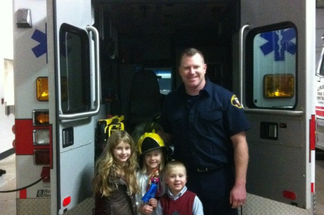 Sgt. 1st Class Keith Knittel, Olympia, Wash. Army Career Center recruiter and volunteer firefighter, poses with his kids in his volunteer uniform. Knittel volunteers as a firefighter to serve his local community and help him find quality Army Reserve enlistees.