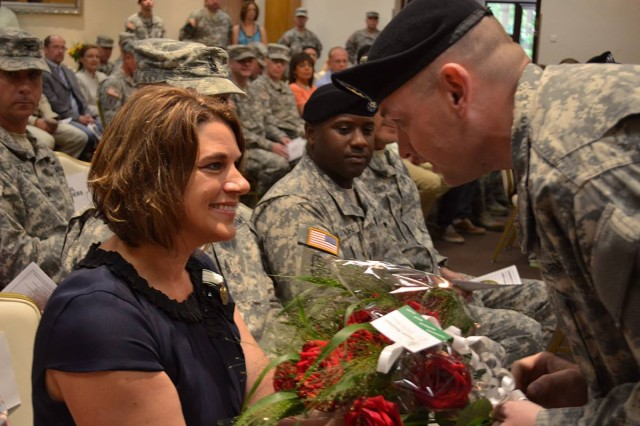 U.S. Army Sgt. Garrett, 598th Transportation Brigade, presents Kristen Redding with a bouquet of red roses during the 598th Transportation Brigade's change of command ceremony Aug. 7 at the Sembach Community Activity Center. The roses are in bloom symbolizing the brigade's gratitude and affection for the many sacrafices she has made for the brigade, its members and her husband, Col. Matthew D. Redding. (U.S. Army photo by A.J. Bosker)