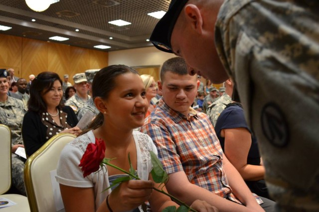 U.S. Army Sgt. Garrett, 598th Transportation Brigade, presents Gracie Redding with a single red rose during the 598th Transportation Brigade's change of command ceremony Aug. 7 at the Sembach Community Activity Center. (U.S. Army photo by A.J. Bosker)