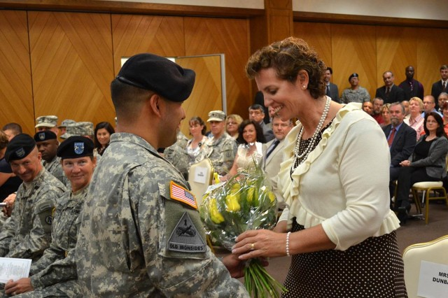 U.S. Army Sgt. Derik Gatton, 598th Transportation Brigade, presents Kate Dunbar with a bouquet of yellow roses during the 598th Transportation Brigade's change of command ceremony Aug. 7 at the Sembach Community Activity Center. The yellow roses are in bud and symbolize the future growth, nuturing and development she will provide to the members of the brigade. (U.S. Army photo by A.J. Bosker)