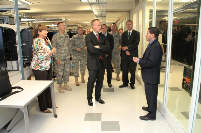 Scott Newman, program director for Systems Engineering and Integration, CERDEC Space and Terrestrial Communications Directorate, shows Under Secretary of the Army Brad R. Carson the C4ISR Systems Integration Laboratory, the site for lab-based risk reduction for systems prior to Network Integration Evaluations at Aberdeen Proving Ground, Md., July 29, 2014.