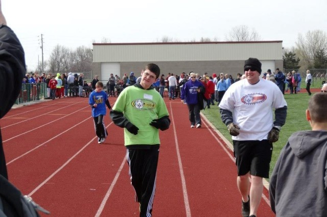 Staff Sgt. Jeffery Kirk, uplift platoon sergeant, Company E, 2nd Battalion, 34th Armor Regiment, right, runs beside his son, Colten, during a Special Olympics track and field competition, April 20, 2013, at Shawnee Heights High School in Tecumseh, Kan. Kirk and his son have been involved with the Manhattan Special Olympics program for several years, with Kirk being a coach for the past two years.