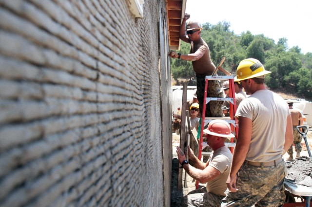 U.S. Army Reserve Engineers with the 672nd Engineer Company from Missoula, Mont., and Navy Seabees with Naval Mobile Construction Battalion 3 from Port Hueneme, Calif., apply stucco to the side of a building they constructed as part of a disaster search zone, a mock town intended to replicate a community devastated by disaster. The disaster search zone is part of the National Disaster Search Dog Foundation's National Training Center (NTC) in Santa Paula, Calif. The NTC is the first facility of its kind in the United States, a comprehensive set of props designed to provide realistic disaster scenarios for training canine search dog teams.