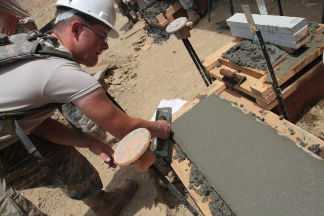 Spc. Corey Hansel, an Army Reserve engineer and native of Rathdrum, Idaho, levels cement as part of a building foundation at the National Disaster Search Dog Foundation's National Training Center (NTC) in Santa Paula, Calif., July 15, 2014. Hansel's unit, the 672nd Engineer Company from Missoula, Mont., spent the summer constructing buildings at the NTC to be used by canine disaster search teams.