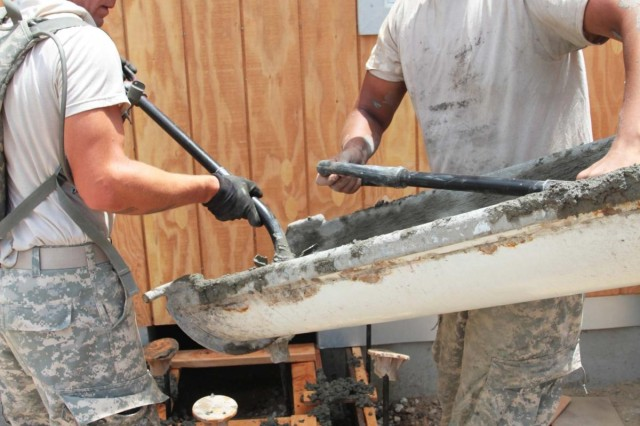 Pfc. Gatlin Lamb (left), from Victor, Mont., and Spc. Steven Hoffman, from Helena, Mont., shovel concrete July 15, 2014, as part of a construction project to build a disaster search zone at the National Disaster Search Dog Foundation's National Training Center. Both Soldiers belong to the 672nd Engineer Company, an Army Reserve unit from Missoula, Mont.