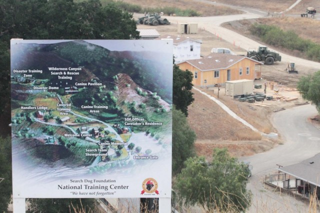 A rendering of the National Disaster Search Dog Foundation's National Training Center sits atop a hill overlooking the 3-acre valley where the center is being built. In the distance stands a building erected by Army Reserve Soldiers from the Missoula, Mont., based 672nd Engineer Company. The Army Engineers broke ground on the construction May 15, 2014. Their partnership with the Search Dog Foundation is part of the Department of Defense's Innovative Readiness Training program.