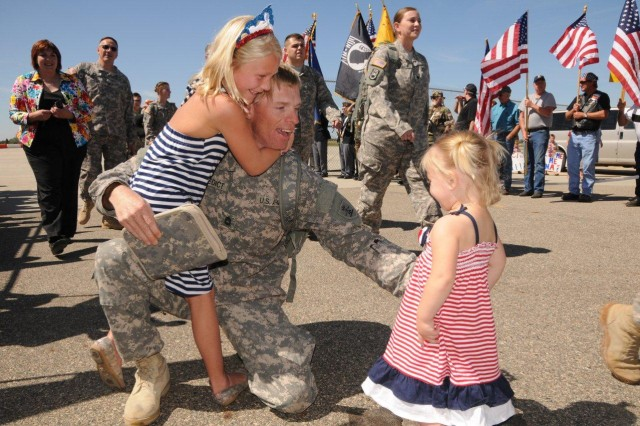 Sgt. 1st Class Jon Benedict embraces his daughters after returning to Fargo, North Dakota from a 2011-2012 deployment with the 188th Engineer Company (Vertical) of the North Dakota Army National Guard. IPPS-A will help active, Reserve and National Guard Soldiers receive timely and accurate pay, even as they change components. (Image courtesy of Sr. Master Sgt. David H. Lipp)