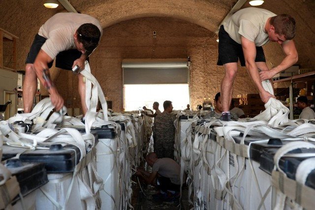 U.S. Army parachute riggers from the 11th Quartermaster Company, 264th Combat Sustainment Support Battalion, 82nd Sustainment Brigade, palletize water for a humanitarian air drop, Aug. 6, 2014, to displaced Yezidis in the vicinity of Sinjar, Iraq.