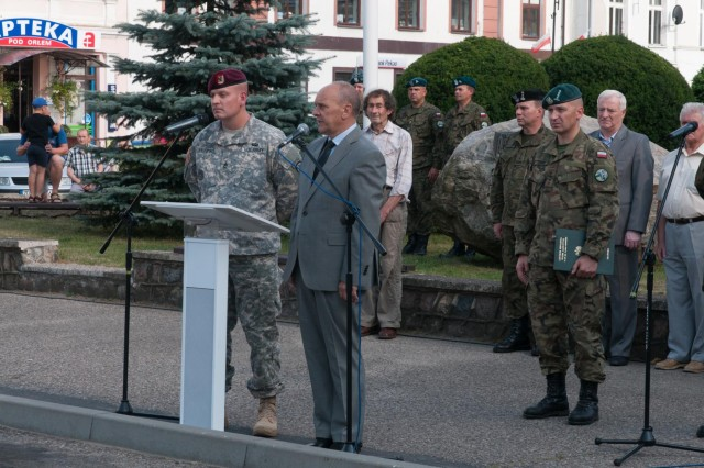 Sgt. 1st Class Gregory Sabiniewicz (left), a Poznan, Poland, native and the logistics non-commissioned officer-in-charge assigned to the 1st Squadron, 91st Cavalry Regiment, 173rd Airborne Brigade, interprets a speech in Drawsko Pomorskie, Poland, given by Mayor Zbigniew Ptak during a ceremony Aug. 1, 2014, honoring the 70th anniversary of the Warsaw Uprising. The Warsaw Uprising was a resistance movement against Nazi Germany during World War II, which lasted from Aug. 1, 1944, through Oct. 2, 1944, and resulted in nearly 200,000 deaths. U.S. and Canadian paratroopers were invited to participate in the ceremony as part of Operation Atlantic Resolve, combined military forces training designed to foster cohesive relationships between allies and demonstrate a commitment to NATO obligations.