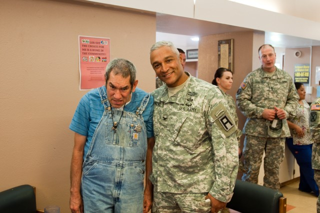Col. Raul Gonzalez, 5th Armored Brigade commander, poses with a resident during a community outreach event to El Paso State Supported Living Center, recently. The 5th Armored Brigade Soldiers received a tour of the facilities and participated in the recreational workshop assembling and disassembling electronics. (Photo by Capt. Jenni Armstrong, 5th Armored Brigade, Division West Public Affairs)