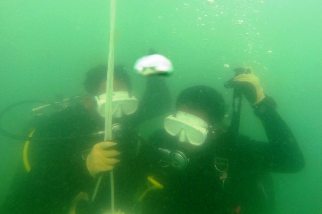 Two Cambodian Mine Action Center divers descend with blacked-out masks simulating zero-visibility conditions during dive training off the coast of Koh Rong, Cambodia, during a 36-day event focused on building their in-water confidence, as well as establishing their basic unit sustainment programs.