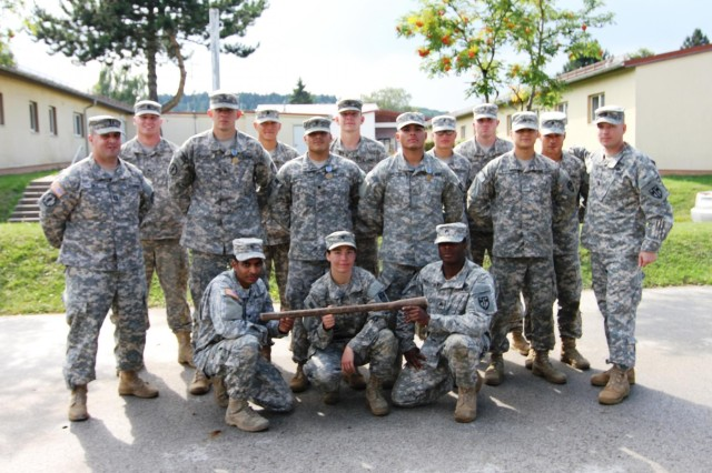 "Capt. Tide Gile, commander of the 527th Military Police Company (far left) and 1st Sgt. Chris Allison (far right) pose with the competitors of the ""STRIKE DEEP"" Mogadishu Mile competition designed to test Soldiers' physical endurance and knowledge of level 1 skills. The winners, centered left to right, were Sgt. Donald Heavener, Spc. Esteban Vazquez, and Pfc. Ariel Galvan. Spc. Abraham James, Spc. Sara Terrell and Sgt. Nicholas Middleton (kneeling in front from left to right) were awarded the BAB bat for continuing the competition regardless of several difficulties and injury July 23 at Hohenfels, Germany. (Photo by Staff Sgt. Christina J. Turnipseed, 18th MP Public Affairs)"