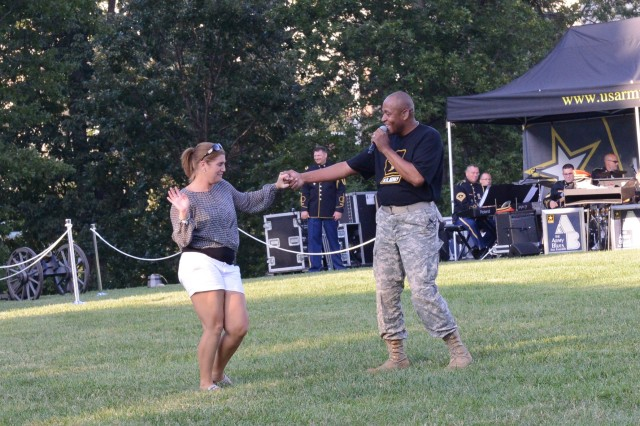 "Courtney A. Dock, Joint Base Myer-Henderson Hall Public Affairs Media Relations chief and Master Sgt. Caleb B. Green, U.S. Army Band ""Pershing's Own"" singer, dance during Twilight Tattoo on Whipple Field, JBM-HH, Va., Aug. 13, 2014."