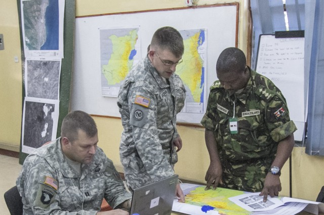 Salima, Malawi—Capt. Paul Wiles, intelligence officer, 4th Brigade Special Troops Battalion, 4th Infantry Brigade Combat Team (left), Capt. Joshua Van Buskirk, intelligence officer, New Hampshire Army National Guard (middle), and Capt. Olly Nyirenda, intelligence officer, Swaziland Defense Force (right), conduct an initial mission analysis while they perform the role of the U2, intelligence cell, during Southern Accord 14, July 17, 2014. SA 14 brings together Southern African partner nations and the U.S. to foster security cooperation while improving combined joint planning capabilities.