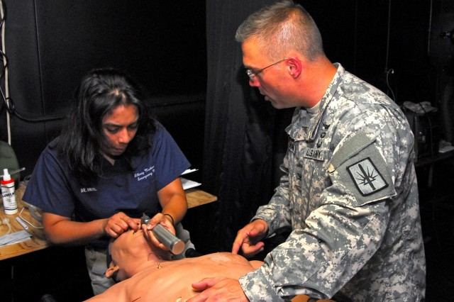 Dr. Anar Patel, an emergency doctor at Albany Medical Center, N.Y., slowly works a laryngoscope through the throat of a mannequin in order to open the air passage and place an endotracheal tube into the lungs, so that a bag-mask ventilator can be applied to assist the patient's breathing, while New York Army National Guard State Surgeon Col. James Coleman, a Saratoga Springs, N.Y., resident, looks on, during training on Aug. 5, 2014, at Camp Smith Training Site in Cortlandt Manor, N.Y. Patel and another resident doctor were on hand at Camp Smith during Medical Command's annual training. The doctors were invited to come to Camp Smith to become familiar with the Army methods and procedures of operating a field aid station, and to give help train members of the New York Army National Guard Medical Command.